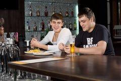 Två män som kopplar av tycka om en afton på baren Arkivbilder