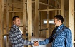 Två män som skakar händer i ett halva konstruerat hus Arkivbilder