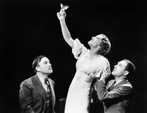 Två män som stöttar en kvinna som lyfter hennes vinexponeringsglas (alla visade personer inte är längre uppehälle, och inget gods Royaltyfria Foton