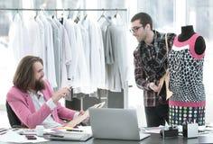 Tv? modeformgivare arbetar p? att skapa kl?der f?r kvinna` s i studion fotografering för bildbyråer