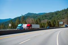 Två moderna kulöra halva lastbilar som kör huvudvägen, vänder sidan - förbi - sidan Arkivfoto