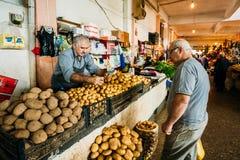Två mogna georgiska män, köpare och återförsäljare som säljer potatisen av nytt Arkivfoto
