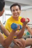 Två mogna män som ler och lyfter vikter i idrottshallen Royaltyfri Fotografi