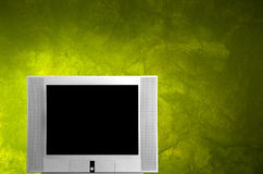 Tv monitor. In a green wall background royalty free stock image