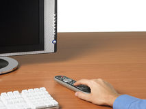 TV monitor, keyboard and hand with remote control Royalty Free Stock Photos