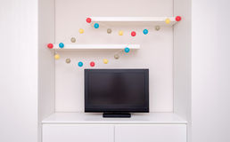 Tv monitor with white furniture and colorful garland. Monitor with white furniture and colorful garland Royalty Free Stock Image