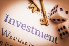 Två mässingstangenter och tärnar på ett grundläggande investeringdokument Arkivfoton