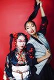 Tv? n?tta geishaflickav?nner: modern asiatisk kvinna och traditionellt b?rande posera f?r kimono som ?r gladlynta p? r?d bakgrund arkivbilder