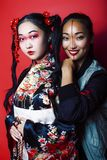 Tv? n?tta geishaflickav?nner: modern asiatisk kvinna och traditionellt b?rande posera f?r kimono som ?r gladlynta p? r?d bakgrund arkivfoto