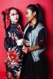 Tv? n?tta geishaflickav?nner: modern asiatisk kvinna och traditionellt b?rande posera f?r kimono som ?r gladlynta p? r?d bakgrund royaltyfri foto
