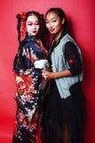 Tv? n?tta geishaflickav?nner: modern asiatisk kvinna och traditionellt b?rande posera f?r kimono som ?r gladlynta p? r?d bakgrund royaltyfri fotografi