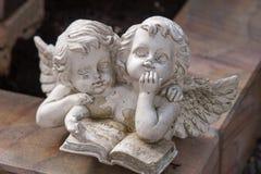 Två änglar som läser en bok Arkivfoto