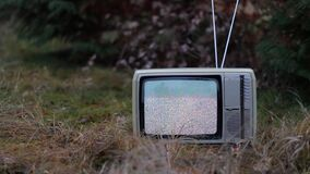 TV no signal in grass. White noise on analogue TV set in outdoor environment stock footage