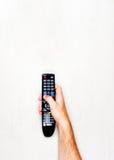 TV noire à télécommande dans la main des hommes sur un fond gris-clair Photo libre de droits