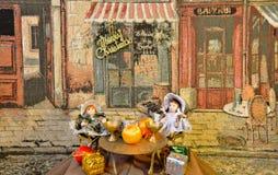 Två nätta dockor som placerar på tabellen nära restaurangen med julgåvorna mot den konstnärliga gobelängbakgrunden Royaltyfria Foton
