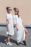 Två nätta gulliga modeflickaflickvänner i vita kappor som poserar för katalog för modekläder i solglasögon på en ljus solig somma Fotografering för Bildbyråer