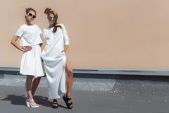 Två nätta gulliga modeflickaflickvänner i vita kappor som poserar för katalog för modekläder i solglasögon på en ljus solig somma Royaltyfri Foto