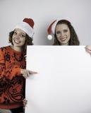Två nätta kvinnor som rymmer tecknet för kopieringsutrymme Arkivfoton