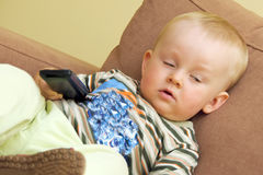 TV overdose. Baby boy overdosing TV watching. Boy is sitting on brown sofa, holding black remote control and is falling asleep Royalty Free Stock Photos