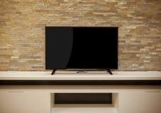 TV på en vit hylla, stenar väggen royaltyfri fotografi