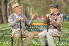 Två pensionärer som talar i, parkerar till varandra Royaltyfri Foto