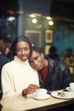 Två personer i kafé som tycker om tidutgifter med de Arkivbild