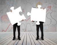 Två personer som rymmer pussel för att förbinda Arkivbilder