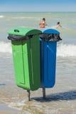 Två plast- avfallåtervinningfack på stranden Arkivbild