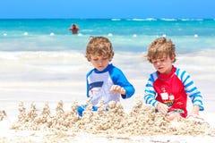 Tv? pojkar f?r sm? ungar som har gyckel med byggande av en sandslott p? den tropiska stranden p? ?n Sunt spela f?r barn fotografering för bildbyråer