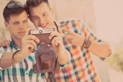 Två pojkar med den retro fotokameran Arkivfoto