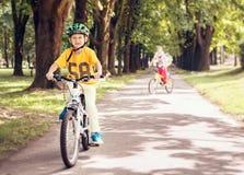 Två pojkar rider en cykel parkerar in Royaltyfri Foto