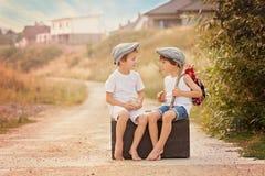 Två pojkar som sitter på en stor gammal tappningresväska som spelar med till Arkivfoton