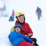 Två pojkar som tycker om vinter, skidar semestern Arkivfoto