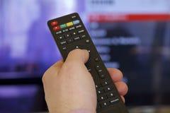 TV ręka i pilot do tv Zdjęcia Stock