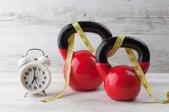 Två röda kettlebells med att mäta bandet och klockan Royaltyfri Foto