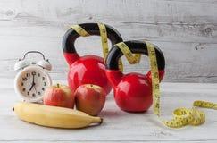 Två röda kettlebells med att mäta bandet, äpplen, bananen och clo Arkivbilder