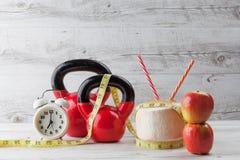 Två röda kettlebells med att mäta bandet som dricker kokosnöten, äpple Arkivfoto