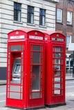 Två röda telefonbås på gatan London Arkivfoto