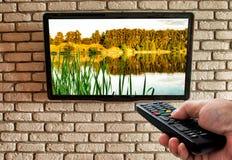 TV remota a disposición y TV en la pared de ladrillo decorativa imagen de archivo