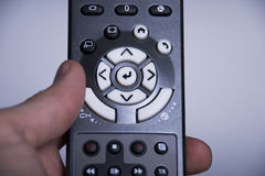 TV remote control. Hand holding a TV remote control Royalty Free Stock Images