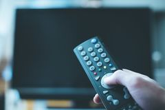 Male hand is holding TV remote control, streaming on a smart TV. TV remote control in the foreground, tv in the blurry background. Film night with vod streaming royalty free stock photo