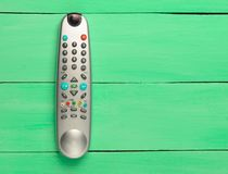 The TV remote control on a green wooden background. Top view.  Stock Photo