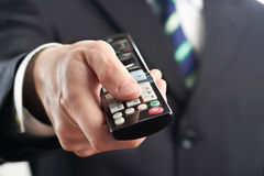 TV remote control in hand of businessman Stock Photo
