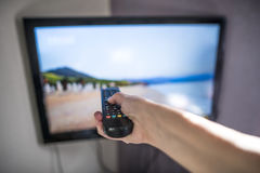 TV and remote control. Hand hold remote Stock Photography