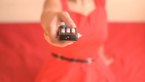 TV remote control in hand. Woman switches TV channels Woman switches TV channels.caucasian young woman in a red dress switches channels on the TV with a remote stock footage