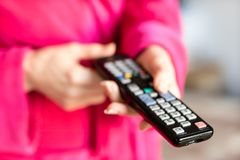 TV remote control held in women& x27;s hands. Switching channels on t. He TV with the remote control. Time of the day, morning royalty free stock photo