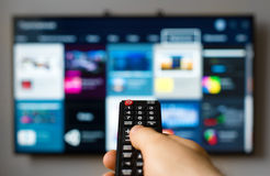TV remote control. Male hand holding TV remote control Royalty Free Stock Photos