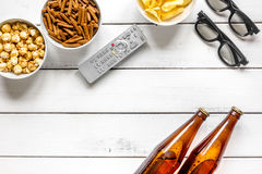 TV remote control, snacks, beer for whatchig film on wooden background top view space for text Stock Images