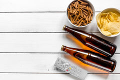 TV remote control, snacks, beer for whatchig film on wooden background top view space for text. TV remote control, snacks, beer for whatchig film on wooden desk Royalty Free Stock Photography
