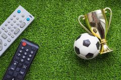 TV remote control and soccer ball with gold cup on the green grass. Program championship football concept stock photos